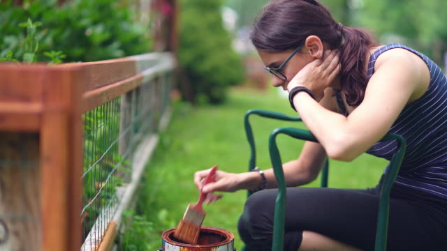 the attractive 15-years-old teenager girl painting the fence at the backyard - recinzione video stock e b–roll