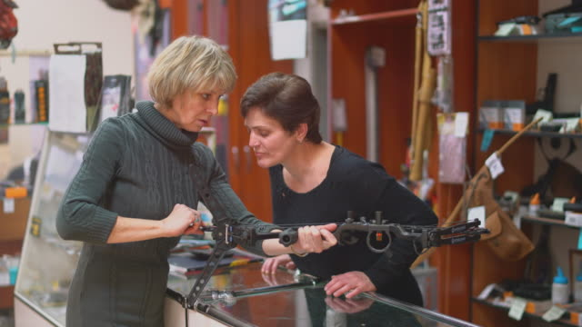 the attractive blonde mature, 50-years-old woman examining the crossbow in the small hunting store, with the assistance of the woman - sales person. - gun stock videos & royalty-free footage