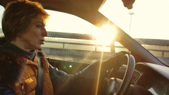 vídeos y material grabado en eventos de stock de la mujer de pelo corto atractivo maduro de 50 años conduciendo el coche en la carretera - 50 54 years