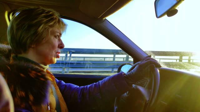 stockvideo's en b-roll-footage met de aantrekkelijke volwassen 50 jaar oude korthaar vrouw besturen van de auto op de snelweg - 50 54 years