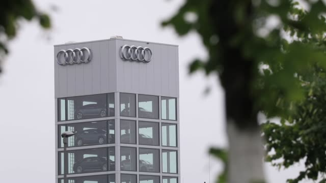 The Audi AG rings logo sits on the automaker's showroom in Berlin Germany on Wednesday July 26 Audi AG automobiles sit in glass display tower at at...