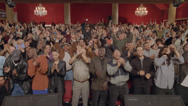 the audience in a theater clap their hands and give a standing ovation as they watch a performance. - laughing stock videos & royalty-free footage