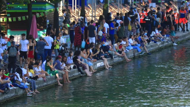 """the audience waits with their feet in the water for the beginning of the film during paris plages launches """"le cinema sur l'eau"""" with the screening... - erfrischung stock-videos und b-roll-filmmaterial"""