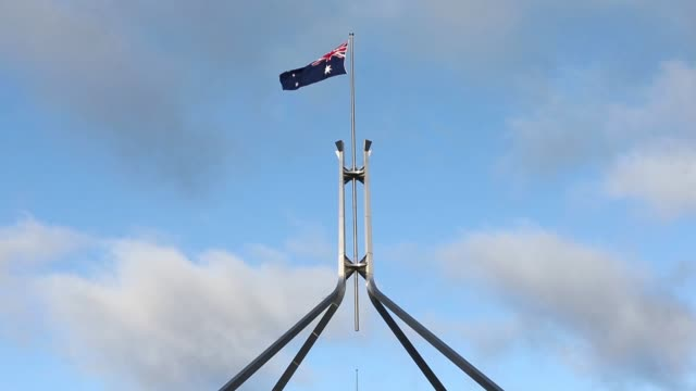 the australian flag flies above parliament house in canberra australia on tuesday july 12 the coat of arms of australia is displayed above the... - canberra stock videos & royalty-free footage