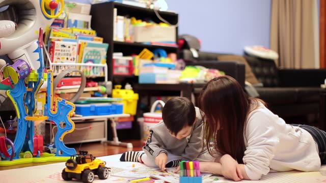 the baby boy drawing with his mother at home - mar bildbanksvideor och videomaterial från bakom kulisserna