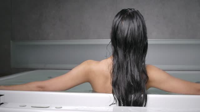 4k bak i en långhårig svart kvinna, hon är trött från att arbeta hårt. hon blötte i badkaret och vilade ögonen. - bekväm bildbanksvideor och videomaterial från bakom kulisserna