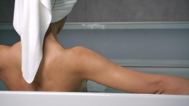 4k bak i en långhårig svart kvinna, hon är trött från att arbeta hårt. hon blötte i badkaret och vilade ögonen. - badkar bildbanksvideor och videomaterial från bakom kulisserna