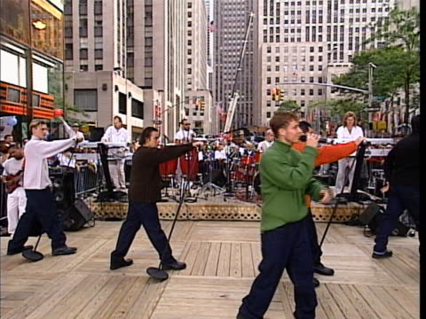 the backstreet boys perform live on an outdoor stage in new york city - music or celebrities or fashion or film industry or film premiere or youth culture or novelty item or vacations bildbanksvideor och videomaterial från bakom kulisserna