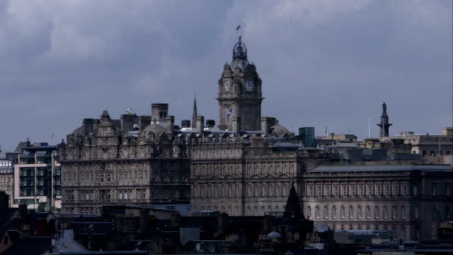 The Balmoral Hotel and Clock Tower looms over the city of Edinburgh Scotland. Available in HD.
