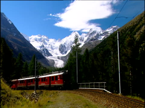 The Banina Express Train drives past camera in the beautiful setting of the Austrian Alps.