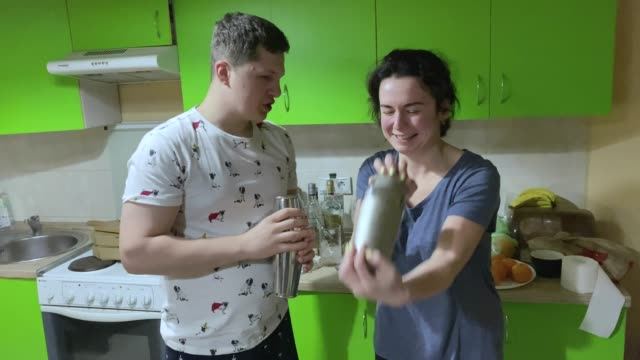 the barman teaches a woman to make a cocktail at a party at home. - shaking stock videos & royalty-free footage