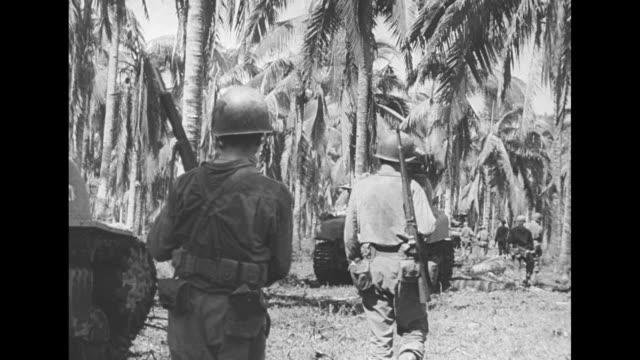 vídeos y material grabado en eventos de stock de vs the barrel of a field gun points toward trees over troops moving right as they walk into the jungle / vs men shoot a mortar and others slowly... - douglas macarthur