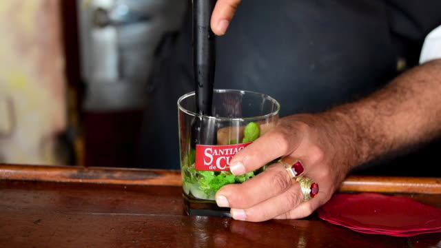 the bartender macerates the mint leaves in a branded glass the glass reads 'santiago de cuba' which is the brand given to the former bacardi rum the... - santiago de cuba stock videos and b-roll footage