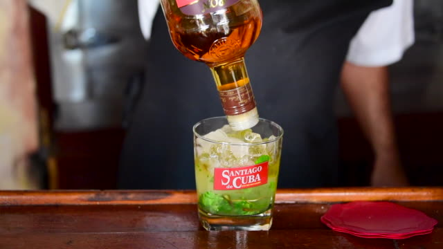 the bartender pours rum into the mix the glass reads 'santiago de cuba' which is the brand given to the former bacardi rum the owners of bacardi rum... - rum stock videos and b-roll footage