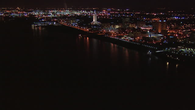 The Baton Rouge skyline and Horace Wilkinson Bridge shine on the Mississippi River at night.