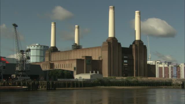 the battersea power plant occupies a riverbank in london. - バタシー発電所点の映像素材/bロール