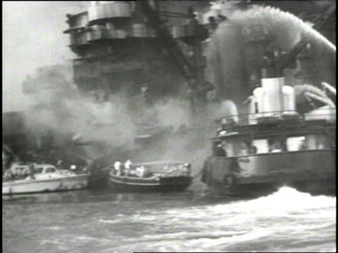 the battleship arizona smoking and burning in pearl harbor after attack / fireboats trying to put out fire smoke / wreckage and clean up of aftermath... - 真珠湾攻撃点の映像素材/bロール