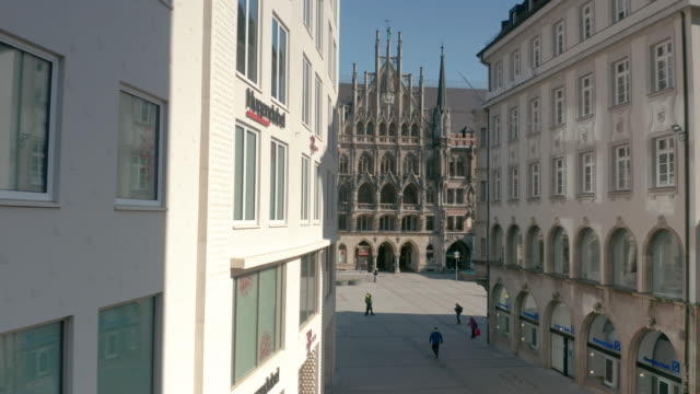 march 31. 2020: the bavarian government has ordered a cut down on social contacts, thus only few people walk over the usually busy marienplatz in the... - baviera video stock e b–roll
