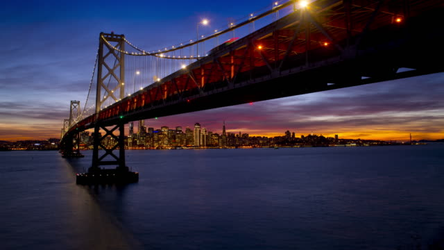 the bay bridge and san francisco at sunset 4k - san francisco oakland bay bridge stock videos and b-roll footage