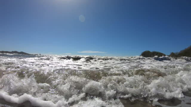 POV of the beach and waves breaking in the surf. - Slow Motion