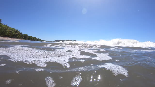 pov of the beach and waves breaking in the surf. - slow motion - goodsportvideo stock videos and b-roll footage