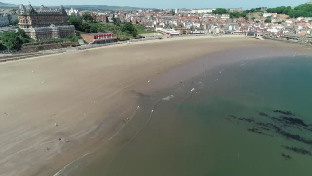 the beach in scarborough on england's eastern coast of england is very quiet on a sunny bank holiday as people heed government calls to avoid tourist... - scarborough uk stock videos & royalty-free footage
