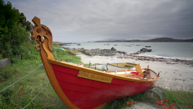 the beach in the village baile mòr, iona, scotland, with traditional fishing boats - pilgrim stock videos & royalty-free footage