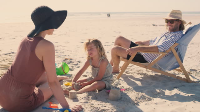 the beach is such a lovely place to be with family - outdoor chair stock videos & royalty-free footage