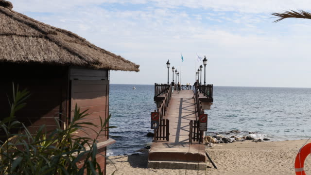 The beach of Marbella with its famous bridge which is located next to the Marbella Club Hotel a couple is walking along
