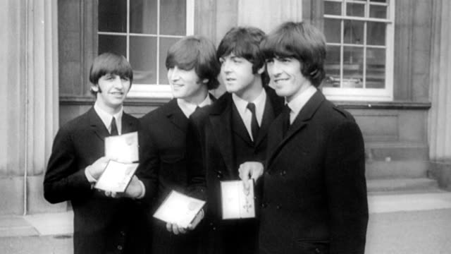 vídeos de stock, filmes e b-roll de the beatles arrive at buckingham palace to receive the mbe award / traffic outside palace / teenagers at gates, screaming as beatles stand with... - 1965
