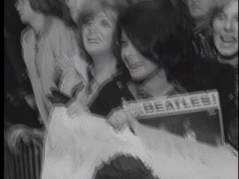 vídeos y material grabado en eventos de stock de the beatles arrive at jfk airport on february 7, 1964 with policemen struggling to hold back the crowd. - 1964