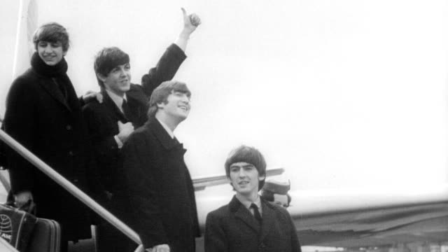 vídeos de stock, filmes e b-roll de the beatles arrive at kennedy airport / plane taxiing on runway / crowds of fans lined up along rooftop screaming and waving / the beatles walk down... - 1964