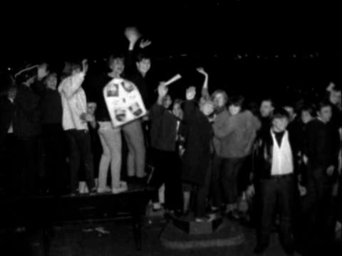 """the beatles arrive back from us tour:; england: london: ext / night fans onto roof: one on """"no waiting"""" sign: 2 on another sign: 2 cowboy kids on... - ポピュラーミュージックツアー点の映像素材/bロール"""