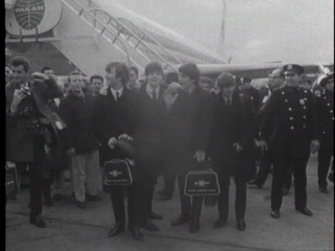 vídeos y material grabado en eventos de stock de the beatles, arriving at jfk airport on february 7 are greeted by thousands of fans as they deplane. - 1964