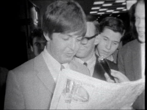 the beatles get mbe; england: london: lap : paul mccartney looks at paper int down escalator with newspapers neg 16mm brenards 25 secs 16 ft 12.6.65... - paul mccartney stock videos & royalty-free footage