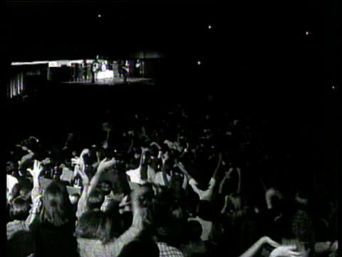 the beatles performing on stage in america / fans in audience, waving and screaming. the beatles on tour in usa on august 18, 1966 - the beatles bildbanksvideor och videomaterial från bakom kulisserna
