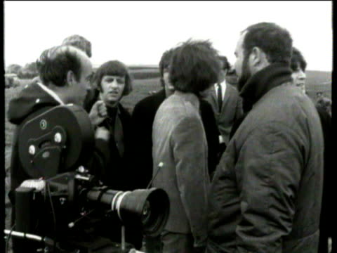 vídeos de stock e filmes b-roll de the beatles performing outside in field during filming of 'help' / film camera and film director richard lester giving instructions on the scene to... - the beatles