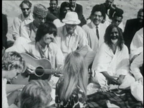 vídeos de stock e filmes b-roll de the beatles playing for a group of people including mia farrow and maharishi mahesh yogi on a beach / india - the beatles
