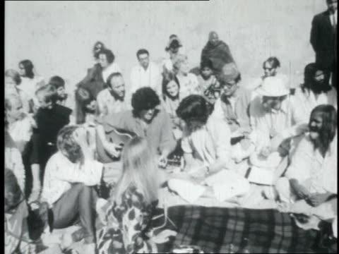 the beatles playing for maharishi mahesh yogi and a group of people on a beach / india - maharishi mahesh yogi stock videos & royalty-free footage