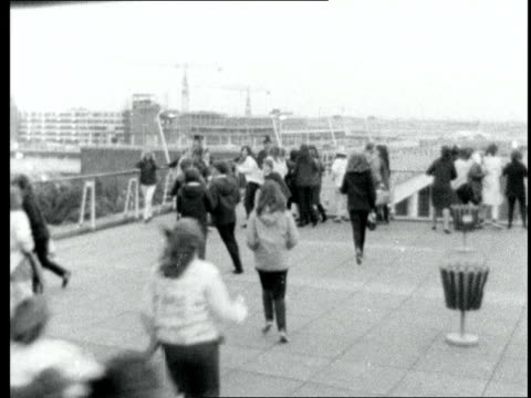 the beatles return from their american tour:; england: london: lap : ext / dawn: fans l-r on roof of airport building: lms plane lands l-r: av girl... - ポピュラーミュージックツアー点の映像素材/bロール
