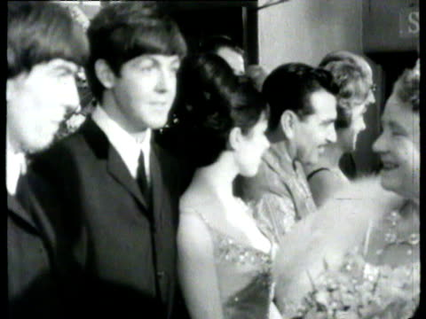 vídeos de stock e filmes b-roll de the beatles talking to the queen mother after the royal variety performance / beatles lined up with others after performance to meet the queen mother... - the beatles