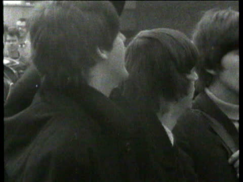 the beatles waiting on airport tarmac to board plane for the bahamas screaming fans lined up waving to band from airport balcony / band posing with... - john lennon stock videos and b-roll footage