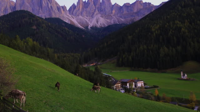 The beautiful Dolomites mountains with sunset light and the St. Johann in Ranui church.