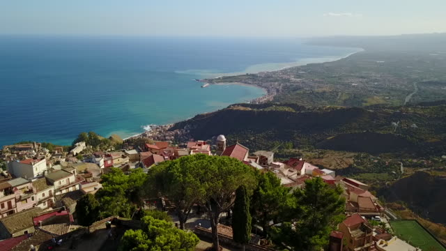 vidéos et rushes de the beautiful view of castelmola town by the sea in sicily, italy - italie