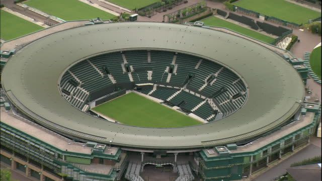 The beautiful Wimbeldon grass tennis courts and stadiums sprawl across green acres in London, England.