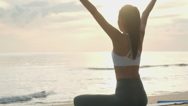 the beauty of nature adding her peacefulness to her yoga. healthy young asian woman with ponytail in front of the sea in lotus pose, meditating at beach on sunset. - cross legged stock videos & royalty-free footage