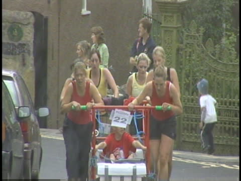the bed race is a grueling race where a team pushed someone in a bed for over three miles - knaresborough stock videos & royalty-free footage