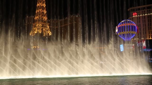 the bellagio fountain on las vegas boulevard at dusk, las vegas, nevada, usa, probably the most unsustainable city in the world, it uses vast quantities of water in the middle of a desert and vast amounts of energy to power this most profligate of cities. - eiffelturm von las vegas stock-videos und b-roll-filmmaterial