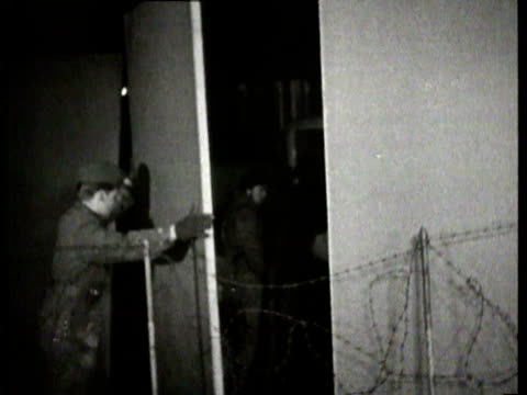 the berlin wall being built at night pieces of the wall are installed barbed wire guards the berlin wall being built at night on november 20 1961 in... - 1961 stock-videos und b-roll-filmmaterial