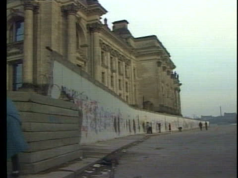 the berlin wall, covered with graffiti and awaiting demolition, wraps around berlin's reichstag. - 1990 stock videos & royalty-free footage